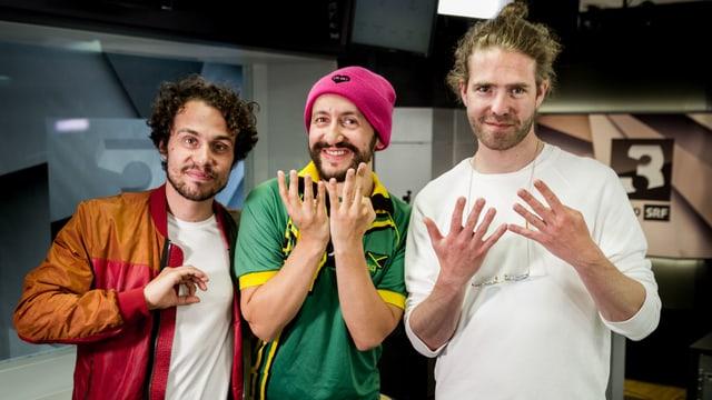 Lo und Leduc sind mit Dr. Mo im SRF 3 Studio und formen mit ihren Fingern die Ziffern 0,7 und 9.