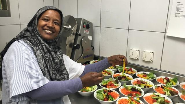 Eine Frau mit Kopftuch bereitet in einer Küche Salatportionen zu.