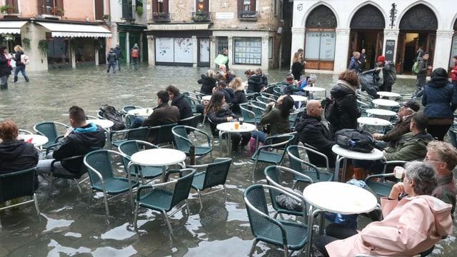 Menschen in Cafes trotz Hochwasser.