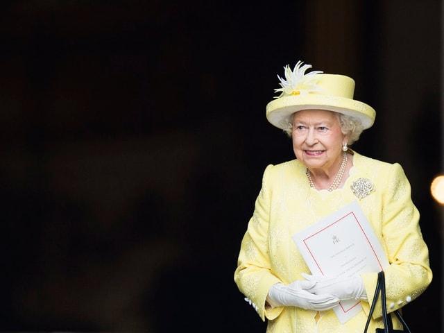 Die Queen mit Hut in einem gelben Kleid