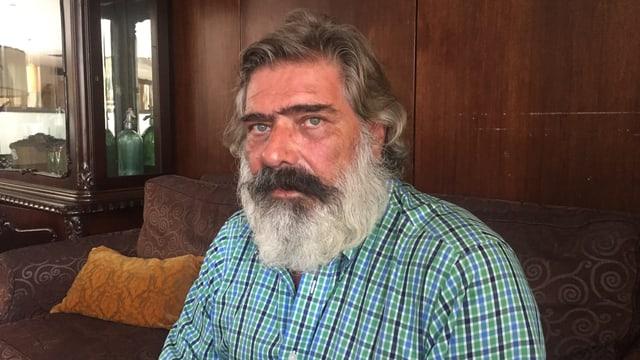 Nikos Giannopoulos, ein Mann mit schwarz-grauem Vollbart, auf einem Sofa.