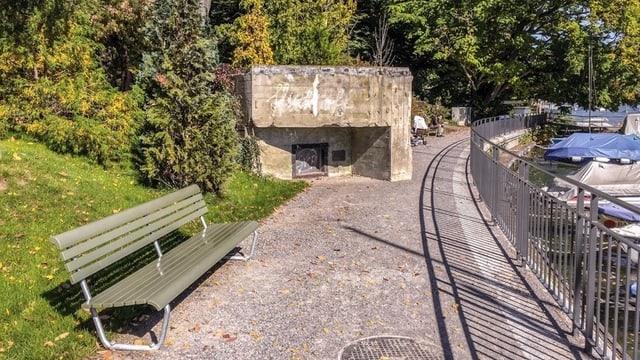 Ein Bunker an der Seepromenade, im Vordergrund ein Kiesweg, links eine SItzbank, dahinter der Bunker und Bäume.