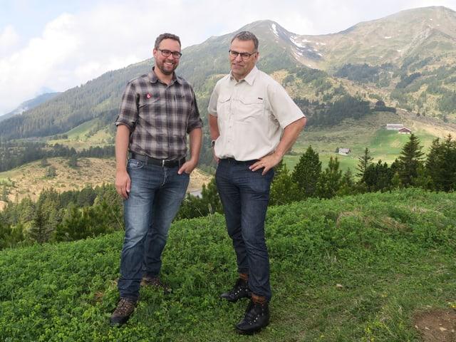 Zwei Männer stehen auf einem Hügel - im Hintergrund Berge und Wälder.