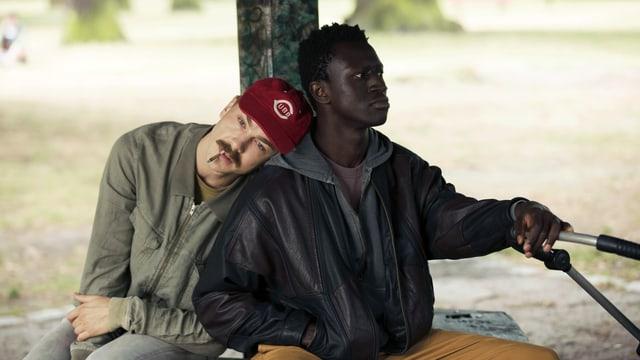 Zwei Männer sitzen in einem Park. Einer schaut in die Ferne, der andere hat den Kopf auf seine Schulter gelegt.