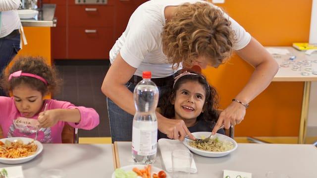 Kinder und Betreuuerinnen beim Mittagessen in einem Zürcher Hort