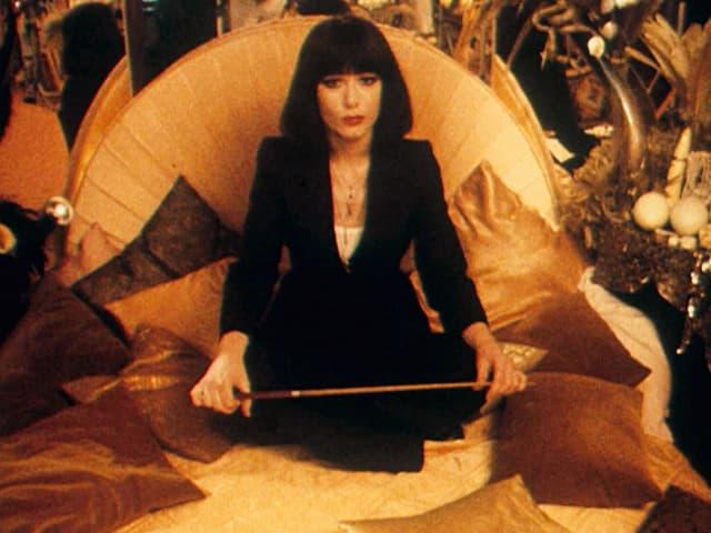 Manon sitzt in Kleidern auf einem opulent ausstaffierten Bett, in der Hand einen Stab.