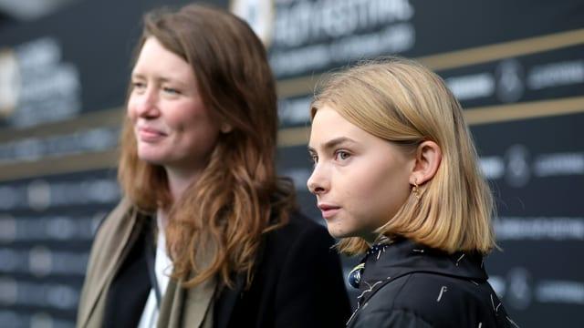 """Eine junge und eine etwas ältere Frau vor deiner Wand mit der Aufschrift """"Zurich Film Festival"""""""
