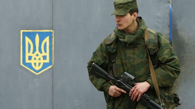 Ein vermutlich russischer Soldat, steht Wache.