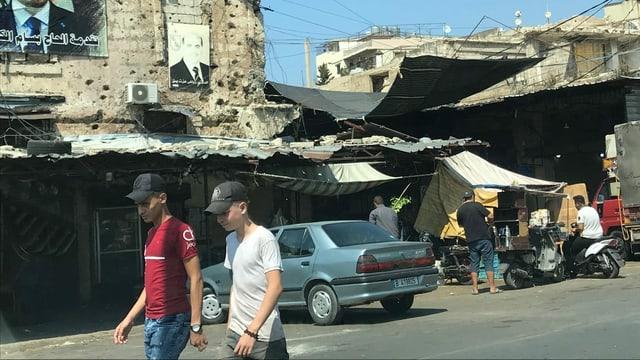 Zerfallende Gebäude, davor junge Menschen.