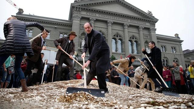Personen vor dem Bundeshaus, sie schaufeln Fünfräppler.