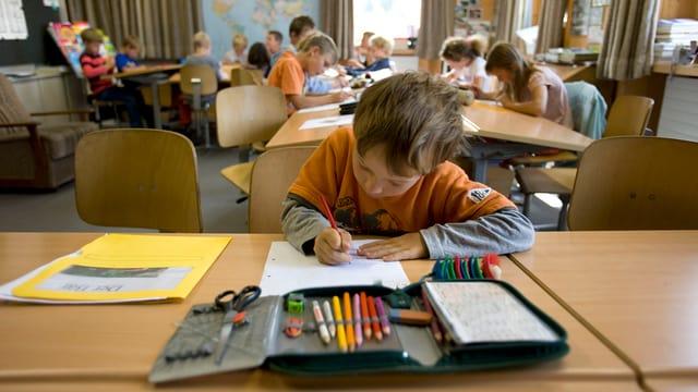 Schüler schreibt etwas auf einem Blatt Papier.