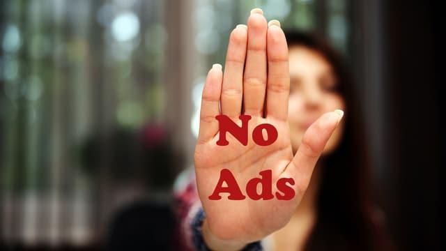 """Eine Frau hält ihre Hand in einer Stop-Geste ins Bild. Auf der Handfläche steht """"No Ads""""."""