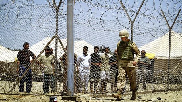 Ein Soldat patroulliert vor einer Absperrung in Abu Ghraib, dahinter stehen Inhaftierte.
