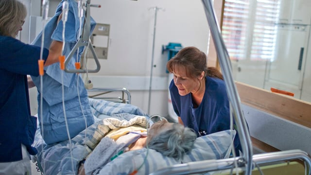 Zwei Krankenschwestern kümmern sich um eine ältere Frau im Spitalbett.