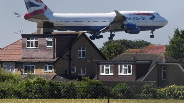 Jumbo fliegt knapp über Häuser am Flughafen Heathrow