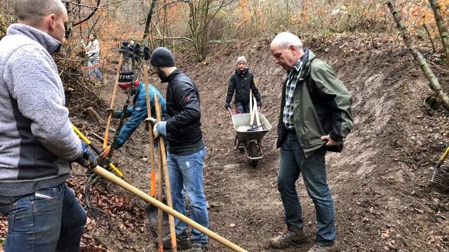 Frauen und Männer arbeiten am Trail im Wald.