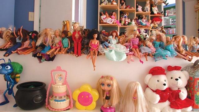 Eine Reihe von Barbies und andere Puppen werden in einem Zimmer präsentiert.