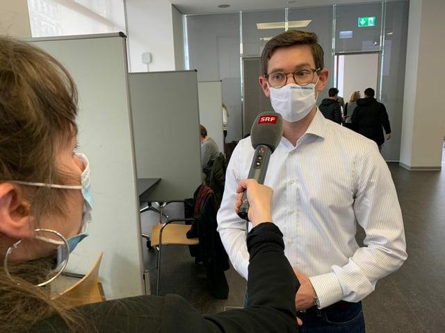 Reporterin interviewt Mann mit Schutzmaske.