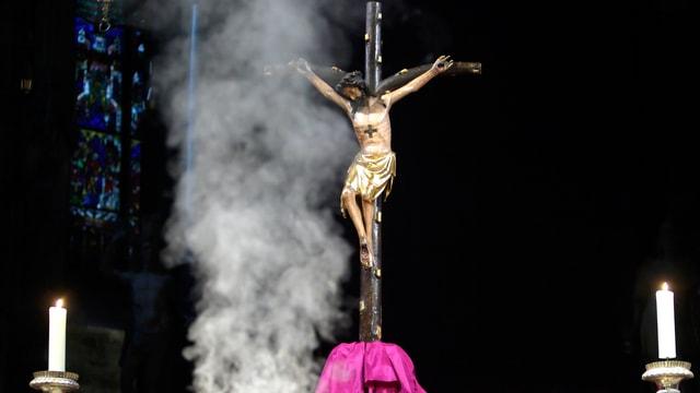 Jesus-Kruzifix, aufsteigender Weihrauch und zwei brennende Kerzen