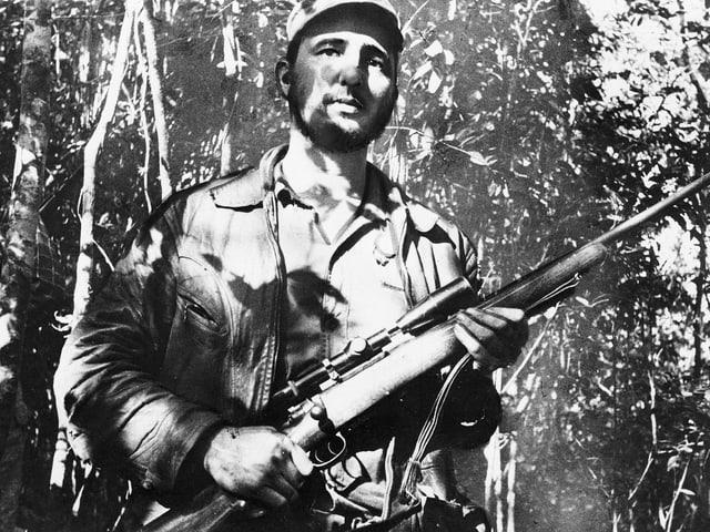 Junger Fidel Castro mit Gewehr in der Hand im Dschungel