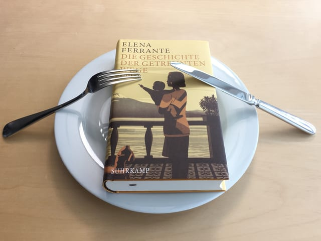 Band 3 Die Geschichte der getrennten Wege von Elena Ferrante liegt auf einem weissen Teller. Messer und Gabel signalisieren, dass Annette König davon nicht genug kriegt.