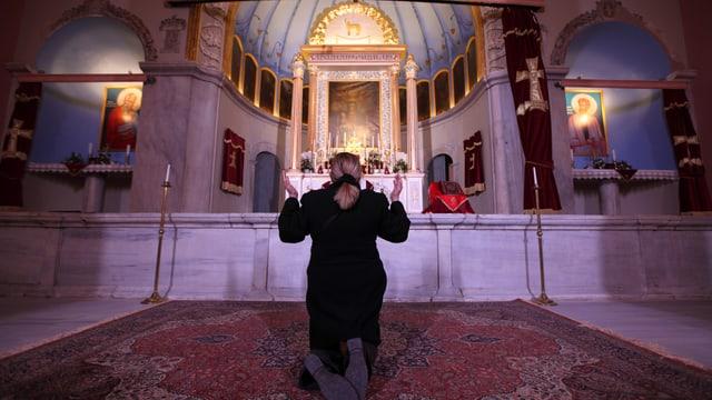 Eine Frau kniet mit erhobenen Händen vor einem Altar in einer Kirche
