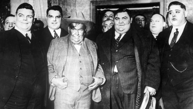 Übergewichtige Männer in Anzügen auf einem Schwarzweissbild aus den 1930er-Jahren.