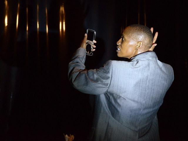 Mamela Nyamza blickt in einen Spiegel und fährt über ihren kahlgeschorenen Kopf, dabei trägt sie ein Männersacko.