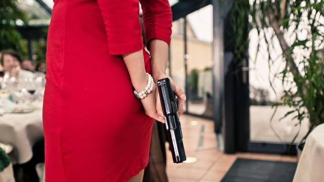 Eine Frau im kurzen roten Kleid von hinten. In der Hand hat sie eine Pistole.