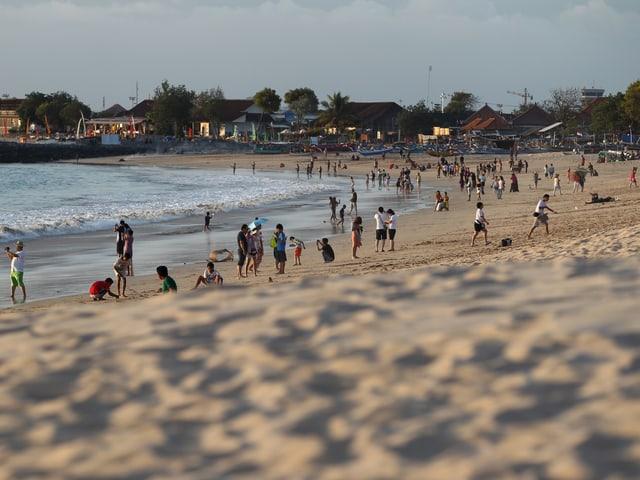 Menschen erholen sich am beliebten Jimbaran-Strand.