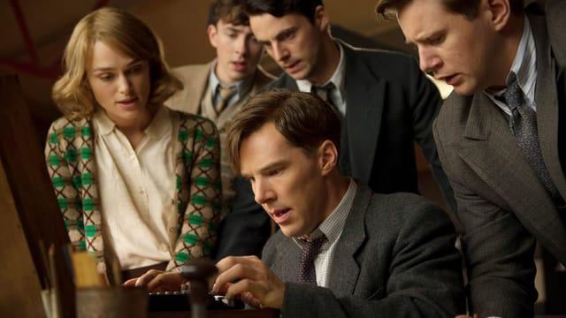 Ein Mann sitzt vor einer Maschine, energisch darauf schreibend. Um ihn herum sind drei Männer, alle in Anzügen, und eine Frau, dargestellt von Keira Knightley.