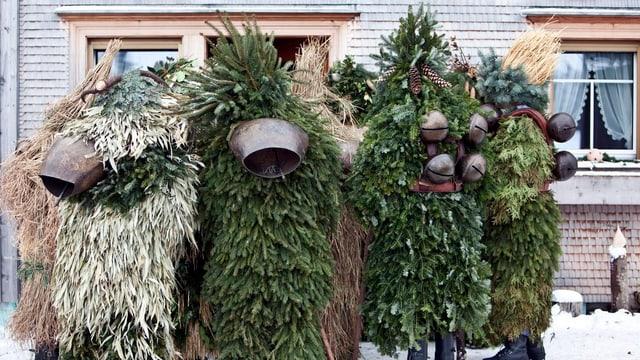 Eine kleine Gruppe von Appenzeller Silvesterchläusen steht in ihren Tannenzweigenkostümen vor einem Haus.