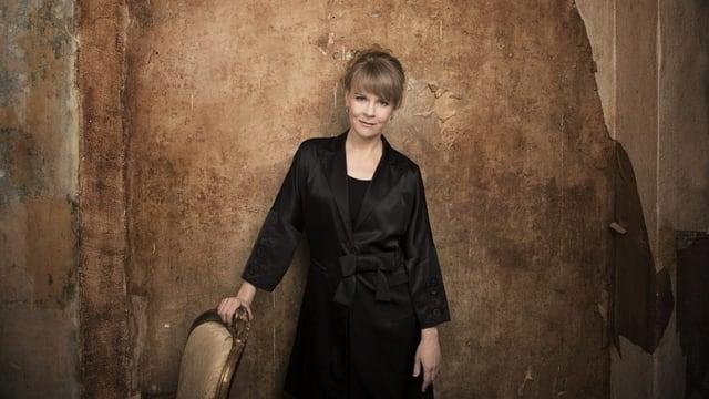 Susanna Mälkki steht vor einer gelb-braunen Wand.