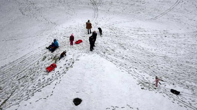 Kinder mit Schlitten und Rodelgefährten auf einer dünnen Schneeunterlage in Bern
