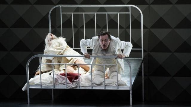 Die beiden Opernsänger auf einem Bett mit Metallgittern am Kopf- und Fussende.