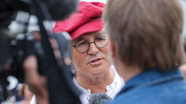 Linard Bardill wird von einem Fernsehreproter interviewt.