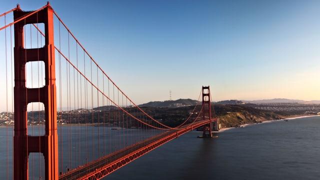 Die rote Brücke im Sonnenlicht, dahinter eine Hügellanschaft.