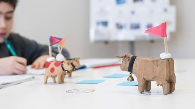 Drei Kühe aus Holz stehen auf einem Tisch. Auf den Figuren sind kleine Fähnchen angebracht.