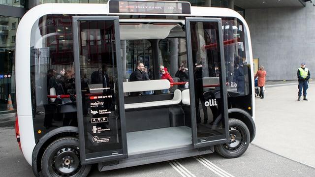 Rechteckiger Bus, der Platz bietet für ca. 10 Personen, steht vor dem Bahnhof Zug mit offen Türen. Daneben sehen zwei Menschen.