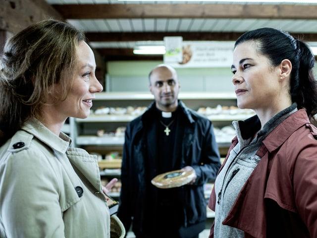 Zwei Frauen sprechen in einem Supermarkt miteinander. Im Hinetrgrund steht ein Mann in Pfarrer-Kleidung.
