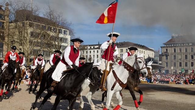 Reiter der Zunft Riesbach umrunden mit der Standarte den Böögg