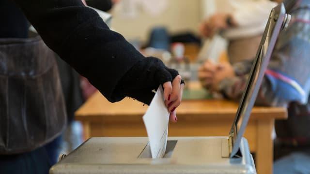 Eine Frau legt einen Stimmzettel in die Urne.