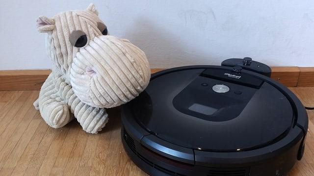 Das Bild zeigt einen aktuellen Staubsauger-Roboter mit einem Stoff-Nilpferd nebendran (dicke Nase!)