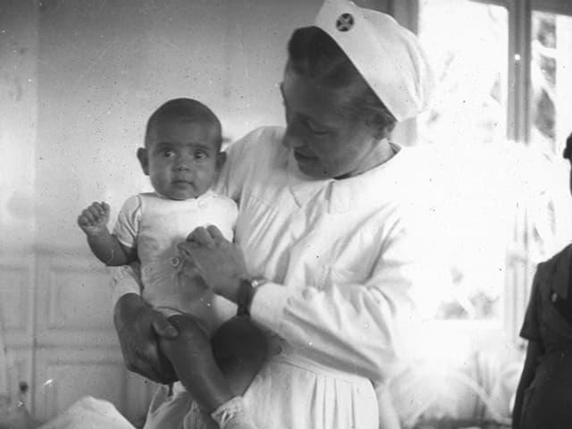 Historische Schwarz-Weiss-Fotografie: Eine Frau in weisser Schwesternuniform hält ein Kleinkind auf dem Arm.