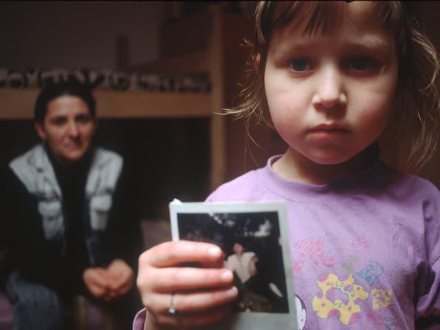 Ein Mädchen aus dem Kosovo mit dem Bild ihres vermissten Vaters.
