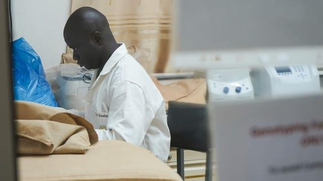 Dunkler Mann in weissem Kittel sitzt in einem Labor.