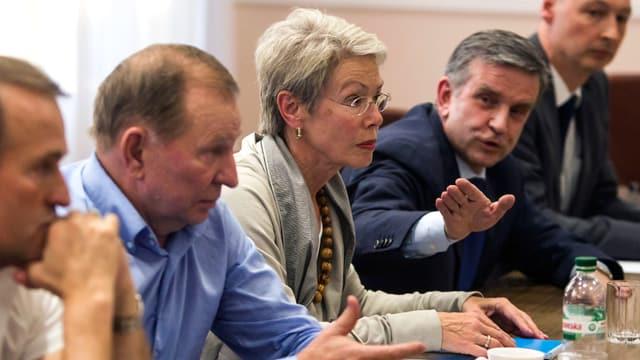 Die drei Erwähnten und zwei weitere Personen sitzen an einem Tisch, Surabow gestikuliert.