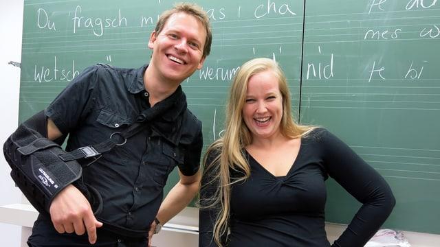 Porträt der beiden Chorleiter vor der grünen Wandtafel im Singsaal.