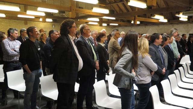 Mehrere Personen stehen vor Stühlen