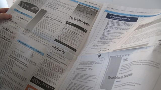Ein Mann studiert die Stellenanzeigen in einer Zeitung.